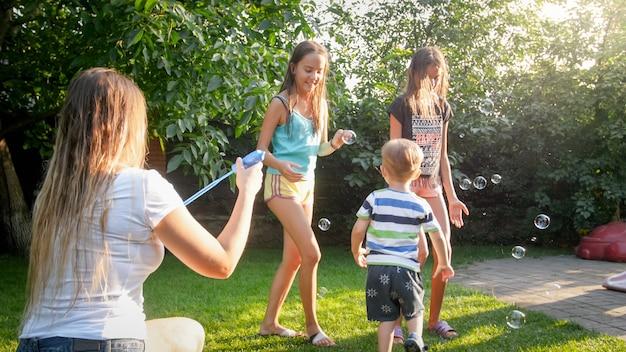 Foto der glücklichen familie, die mit seifenblasen im haushinterhofgarten spielt. familie, die im sommer im freien spielt und spaß hat