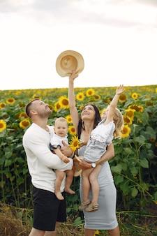 Foto der glücklichen familie. eltern und tochter. familie zusammen im sonnenblumenfeld. mann in einem weißen hemd.