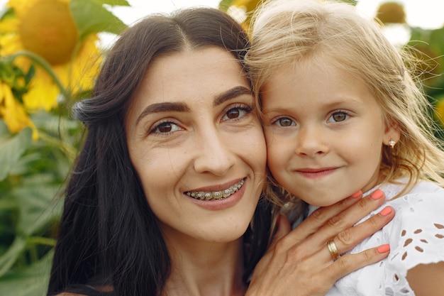 Foto der glücklichen familie. mutter und tochter. familie zusammen im sonnenblumenfeld.