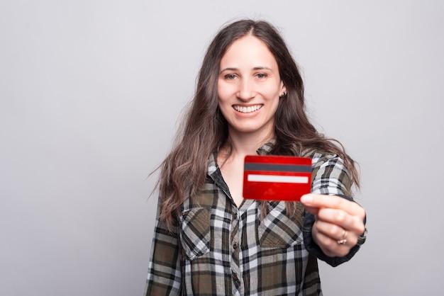 Foto der glücklichen jungen frau, die ihre neue kreditkarte, online-webbanking zeigt