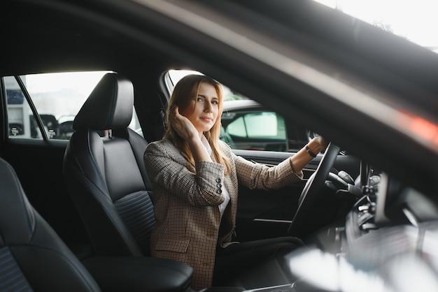 Foto der glücklichen jungen frau, die in ihrem neuen auto sitzt. konzept für mietwagen