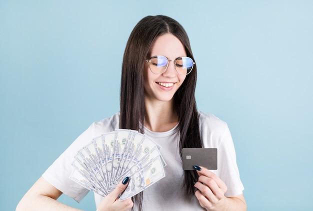 Foto der glücklichen jungen frau, die lokal über blauem hintergrund steht. blick beiseite halten geld und kreditkarte.