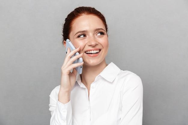 Foto der glücklichen jungen hübschen rothaarigen geschäftsfrau, die lokalisiert über grauer wand aufwirft, die durch handy spricht.