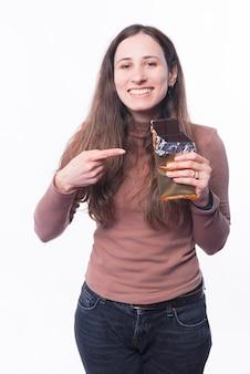 Foto der glücklichen jungen kaukasischen frau, die auf schwarz der schokolade zeigt