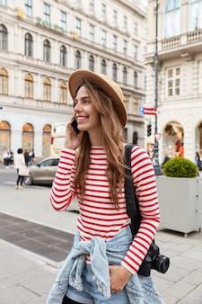 Foto der glücklichen jungen touristin im stilvollen outfit, spaziert in der stadt, hat tour, trägt fotokamera auf der schulter