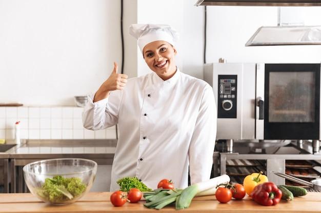 Foto der glücklichen köchin, die weiße einheitliche kochmahlzeit mit frischem gemüse trägt, in der küche am restaurant