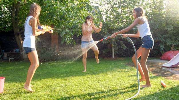 Foto der glücklichen lachenden familie, die wasser mit wasserpistolen und gartenschlauch im hinterhof spritzt. leute, die an heißen sonnigen sommertagen spielen und spaß haben