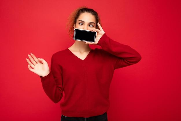 Foto der glücklichen lustigen jungen weiblichen person, die dunkelroten pullover trägt
