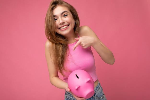 Foto der glücklichen positiven lächelnden jungen netten charmanten erstaunlichen blonden frau, die stylisches rosa top trägt
