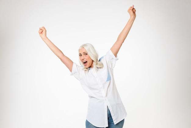 Foto der glücklichen weiblichen rentnerin der 60er jahre mit grauem haar, das ihre arme erhebt und entzückt schreit, lokalisiert über weißer wand