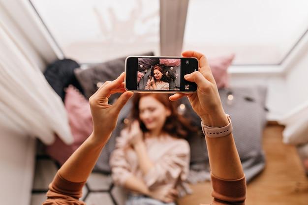 Foto der hände, die telefon während des fotoshootings halten. ingwer-mädchen, das für ihren freund zu hause aufwirft.