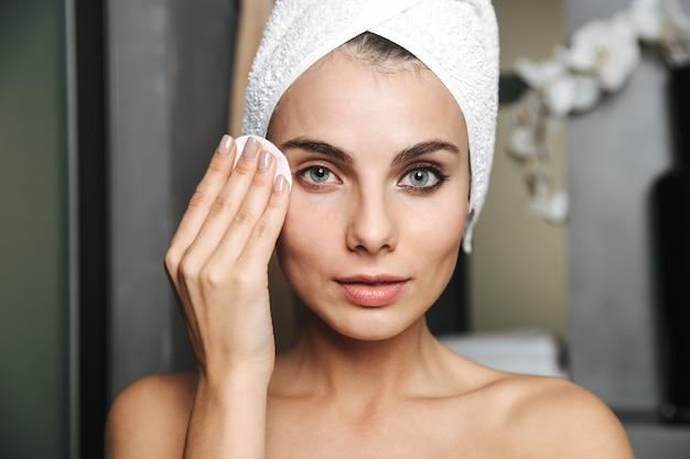 Foto der herrlichen frau mit handtuch auf kopf, die ihr gesicht reinigt und make-up mit wattepad entfernt