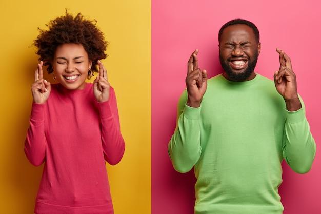 Foto der hoffnungsvollen glücklichen afro america frau und mann drücken die daumen für viel glück, glauben, dass das glück kommen wird, hoffen, dass der wunsch erfüllt wird, antizipieren, dass ein wunder passiert ist, posieren gegen die gelbe und rosa wand