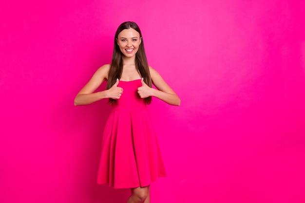 Foto der hübschen dame, die daumen hoch hebt, die gute qualität der produkte anerkennen, tragen helle, schulterfreie, stilvolle, niedliche kleider, die einen lebendigen, rosa farbhintergrund isolieren