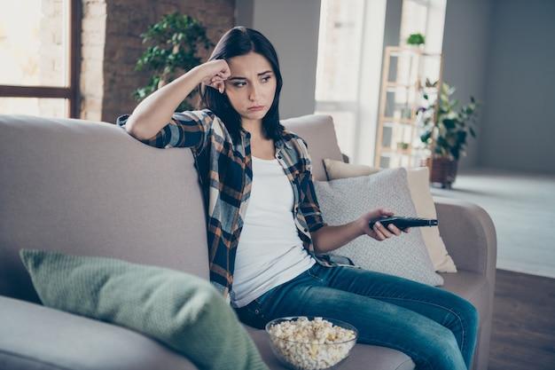 Foto der hübschen dame, die fernbedienung und popcornplatte hält, die vom sitzenden sofa des lieblingsserienendes sitzen, das freizeitwohnungswohnung drinnen trägt