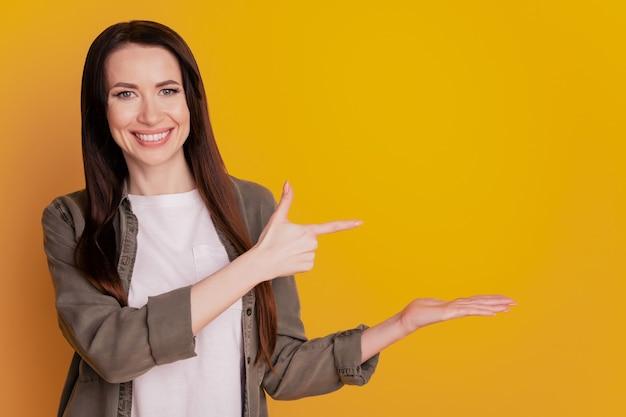 Foto der hübschen dame, die offene handfläche mit dem finger zeigt, kühles angebot isoliert auf gelbem hintergrund