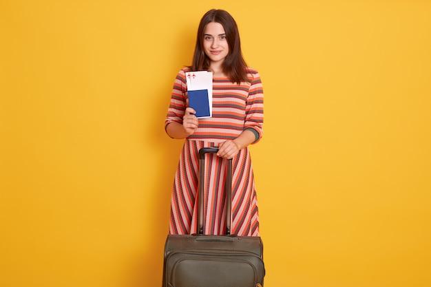 Foto der hübschen dame, die reisepass, tickets und rollendes koffergepäck hält, das im flughafen ist