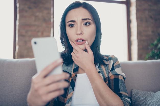 Foto der hübschen dame, die telefon hält, glauben augen nicht, die neue blogbeitrag lesen negative kommentare sitzen gemütliches sofa tragen freizeitkleidung wohnung drinnen
