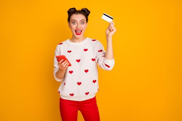 Foto der hübschen dame halten telefonplastikkreditkarte, die online-kauf süchtig macht käufer tragen herzen muster weißen pullover