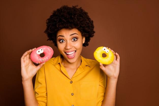 Foto der hübschen dunklen haut lockige dame halten zwei bunte donuts karamellaugen menschliche gesichter verrückte sorglose kindliche stimmung tragen gelbes hemd isolierte braune farbe