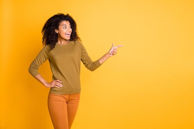 Foto der hübschen dunklen hautverkäuferin, die fingerseite leeren raum vorschlägt, der verkaufspreis des verkaufs vorschlägt, tragen lässige pulloverhosen lokalisierten gelben farbhintergrund