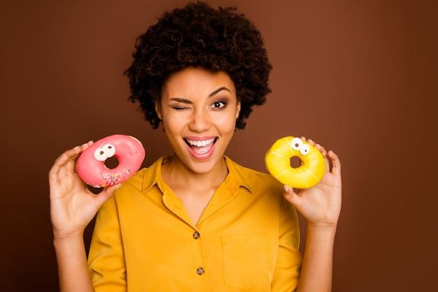 Foto der hübschen dunklen hautwellendame halten zwei bunte donuts karamellaugen menschliche gesichter verrückt sorglos blinkend flirty tragen gelbes hemd isolierte braune farbe