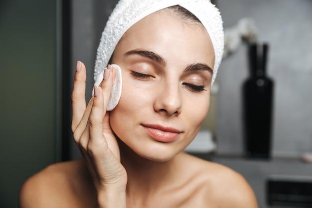 Foto der hübschen frau mit handtuch auf kopf, die ihr gesicht reinigt und make-up mit wattepad entfernt