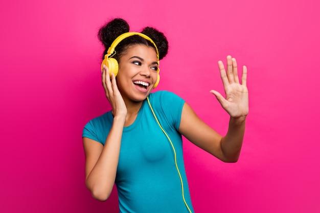 Foto der hübschen funky dame hören musik kopfhörer erhöhen hand tanzen