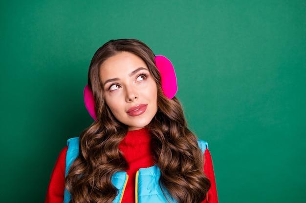 Foto der hübschen hübschen jungen dame verträumt lächelnd neugierig auf leeren raum denken winterurlaub urlaub tragen rosa ohrwärmer blaue weste roter pullover isoliert grüner farbhintergrund