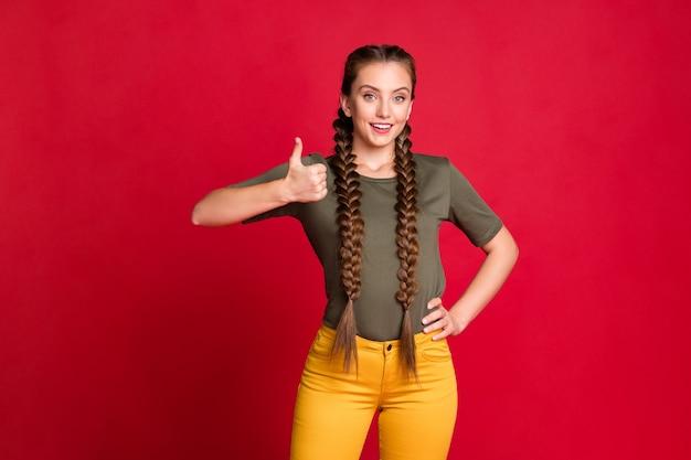 Foto der hübschen jugendlich vorbildlichen dame, die übereinstimmung gute qualität des produkts ausdrückt, das daumen hoch trägt, tragen lässige t-shirt-gelbe hose, isolierte rote farbe hintergrund