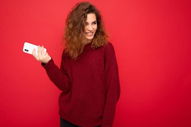 Foto der hübschen lächelnden glücklichen jungen frau mit dem lockigen haar, das dunkelroten pullover lokalisiert auf rotem hintergrund hält, der handy hält, das zur seite schaut und spaß hat.