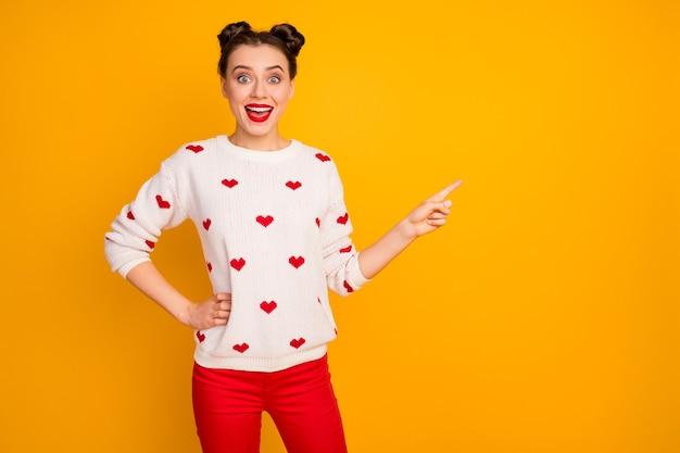 Foto der hübschen lustigen dame, die den leeren raum des fingers anzeigt, der coole verkaufspreise des einkaufszentrums empfiehlt, tragen weißen pullover des herzmusters
