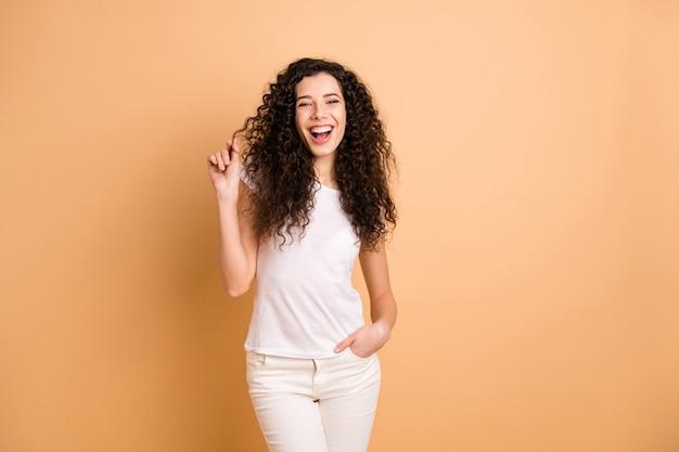Foto der hübschen lustigen dame, die wellige locken des perfekten zustands nach dem besuch des erstaunlichen salonstylisten zeigt, tragen weiße freizeitkleidung, die beigen pastellfarbenen hintergrund lokalisiert