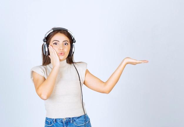 Foto der hübschen netten frau, die musik in kopfhörern hört und hand zeigt.