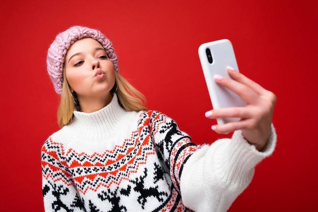 Foto der hübschen positiven jungen blonden frau, die warme strickmütze und warmen winterpullover trägt