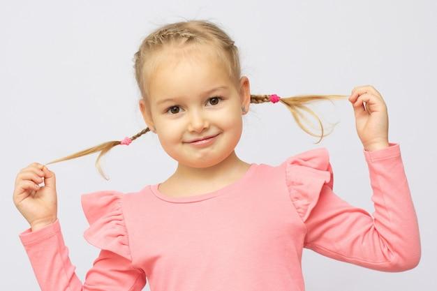 Foto der hübschen schönen kleinen dame, die hände zwei süße schwänze hält, die einen langen neuen shampoo-effekt zeigen, tragen rosa kleid einzeln auf grauem hintergrund