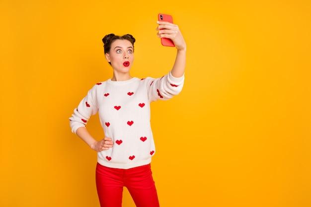 Foto der hübschen verängstigten dame halten telefonhände, die selfies nehmen, die skype-freunde sprechen hören schlechte nachrichten tragen herzenmuster weißen pullover