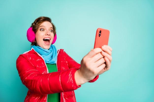 Foto der hübschen verrückten dame mit offenem mund halten telefon gute nachrichten überprüfen mag anhänger abonnenten tragen roten mantel schal rosa ohrhüllen grünen pullover isoliert blaugrün farbe wand