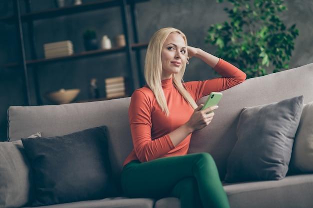 Foto der inländischen stimmung der hübschen blonden dame, die telefonphantasieflug hält, denken sie über neuen kreativen posttext, der bequemes couch lässiges outfit wohnzimmer drinnen sitzt