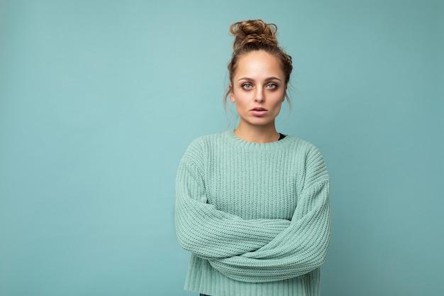 Foto der jungen attraktiven europäischen modeblondinenfrau, die blauen pullover einzeln auf blauem hintergrund mit kopienraum mit ernstem gesichtsausdruck trägt. einfache und natürliche weibliche person.