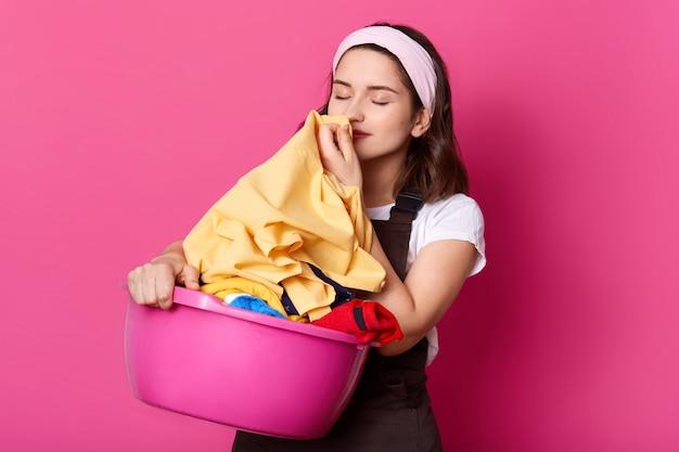 Foto der jungen attraktiven frau, die zu hause arbeitet, trägt t-shirt, braune schürze und haarband, stehend mit rosa becken mit sauberem leinen lokalisiert auf rosenwand im fotostudio, riecht frische kleidung.