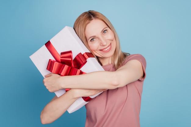 Foto der jungen attraktiven frau glückliches positives lächeln umarmt kuscheln geschenkbox einzeln auf blauem farbhintergrund