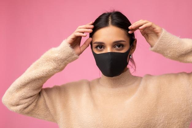 Foto der jungen attraktiven frau mit handgemachter baumwollstoff-gesichtsmaske isoliert über bunter hintergrundwand. schutz vor covid-19.