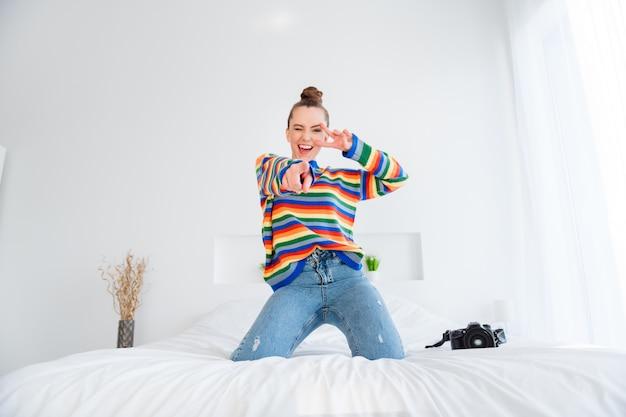 Foto der jungen dame, die zu hause spricht, videoanruf zeigt v-zeichen direkter finger auf kameraschlafzimmer im innenbereich