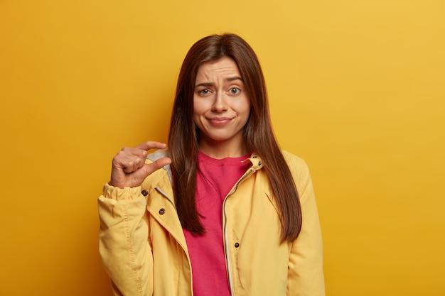 Foto der jungen dunkelhaarigen frau zeigt sehr kleine größe mit den fingern, zeigt winziges maß, erzählt von gesunkenen preisen und geringem gehalt, zieht verwirrt die augenbrauen hoch, trägt gelbe jacke