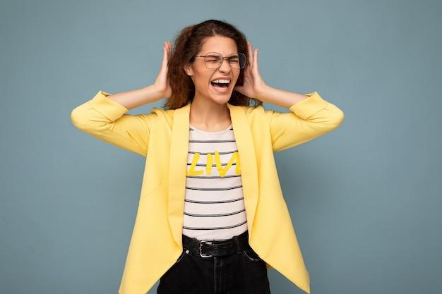 Foto der jungen emotional wütenden attraktiven brünetten lockigen frau mit aufrichtigen emotionen, die stylisch trägt