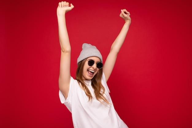 Foto der jungen emotionalen positiven glücklichen attraktiven dunkelblonden frau mit aufrichtigen gefühlen tragend