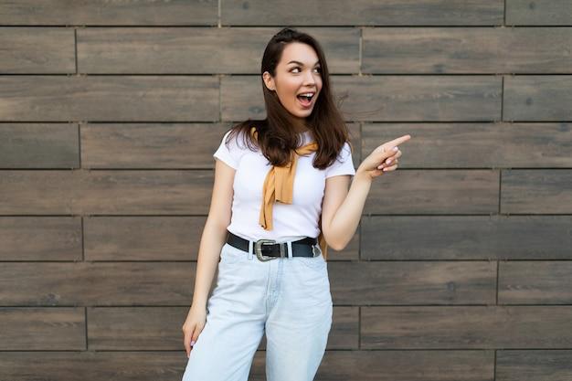 Foto der jungen emotionalen positiven überraschten schönen brunet-dame, die legere kleidung trägt, die auf der straße nahe der wand steht und auf leeren raum zeigt. lifestyle-konzept.