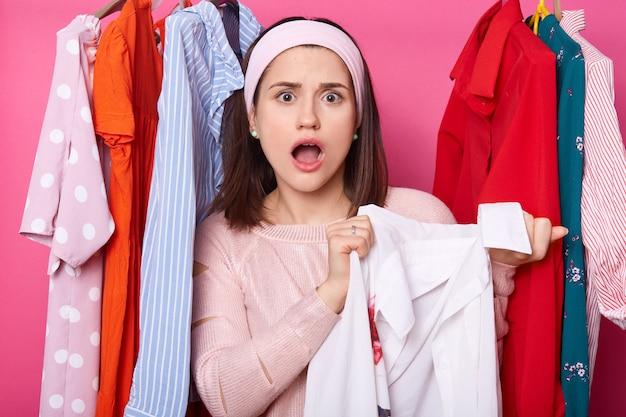 Foto der jungen entsetzten frau steht zwischen aufhängern mit bunter kleidung. schöne dame überrascht mit preisschild des kleides. frau mit geöffnetem mund hält weißes hemd. shopping und fasion konzept.