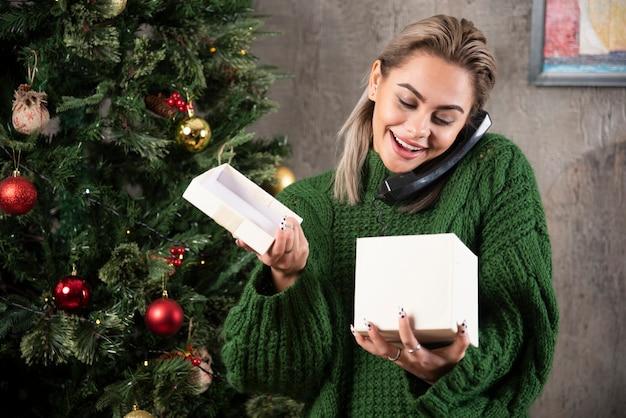 Foto der jungen frau, die am telefon spricht und glücklichen ausdruck hat